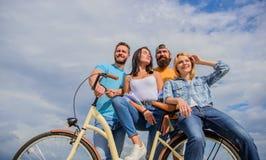 Anteil- oder Mietfahrradservice Firmenstilvolle junge Leute geben Himmelhintergrund der Freizeit draußen aus Fahrrad als bester F stockfoto