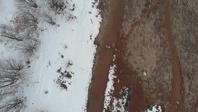 Antena: acople o passeio na estrada secundária com neve e árvores, diretamente acima da vista, movimento lento filme