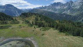 Antena adelante sobre el valle del bosque de la montaña del lago que revela alpino azul en verano soleado con las nubes Montañas  metrajes