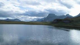 Antena al revés sobre el valle de la montaña del lago que revela alpino en oscuridad o amanecer nublada del día Las montañas de E metrajes