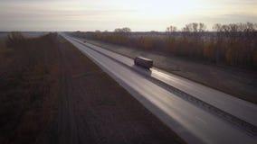 Antena: camiones de reparto que conducen hacia el sol el coche con el envase monta en el camino a la puesta del sol Paseos del ca almacen de video