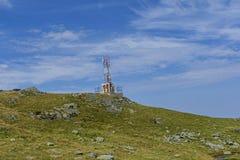 Antena celular de las comunicaciones de las telecomunicaciones de las comunicaciones en el top de las montañas con el refugio oxi Fotografía de archivo