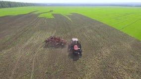 Antena czerwony ciągnikowy wirować na zaoranej części rolniczy pole zdjęcie wideo