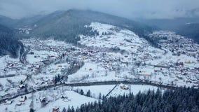 Antena da localidade habitada nas montanhas no inverno Construções e casas da aldeia da montanha em inclinações nevados do monte video estoque