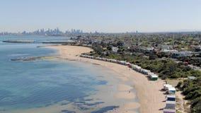 Antena de Brighton Bathing Boxes en Melbourne del océano con la ciudad, órbita almacen de metraje de vídeo