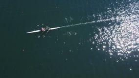 Antena de entrenamiento del remero El hombre y la mujer baten el agua azul chispeante en Sunny Day almacen de video