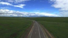 Antena de los camiones de reparto que conducen en el camino vac?o en campo hermoso con la hierba verde en el verano almacen de metraje de vídeo