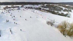Antena de los esquiadores y de los snowboarders que disfrutan de deportes de invierno en las colinas de la nieve con la copia y e almacen de video