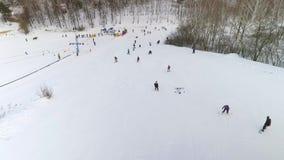 Antena de los esquiadores y de los snowboarders que resbalan abajo de cuesta nevosa y que montan para arriba con el remonte almacen de video
