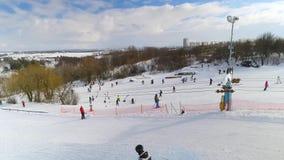 Antena de los esquiadores y de los snowboarders que resbalan abajo de cuesta nevosa y que montan para arriba con el remonte almacen de metraje de vídeo