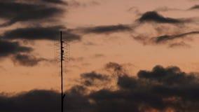 Antena de televisión vieja contra el vídeo del timelapse del cielo de la puesta del sol metrajes