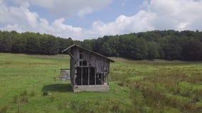antena del abejón de la órbita del ángulo bajo 4k de la choza de madera en las montañas verdes, por un bosque almacen de metraje de vídeo