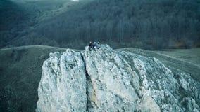 antena del abejón 4k Caminar a la gente joven que se sienta en un acantilado metrajes