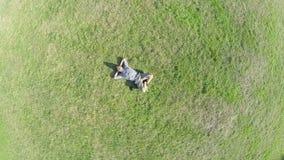 Antena del hombre que miente en la hierba, enfoque-hacia fuera extremo, globo de la tierra almacen de metraje de vídeo
