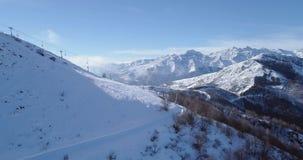 Antena del lado en el pico de montaña blanco de la nieve en la elevación de silla del esquí del esquiador del invierno que revela metrajes