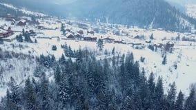 Antena del lugar habitado en las montañas el invierno Edificios y casas del pueblo de montaña en cuestas nevosas de la colina almacen de metraje de vídeo