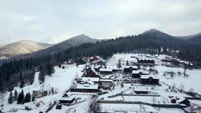 Antena del lugar habitado en las montañas el invierno Edificios y casas del pueblo de montaña en cuestas nevosas de la colina almacen de video