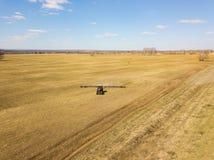 Antena del tractor rojo con una paleta arrastrada para segar y escardar los campos para la agroindustria del color amarillo debaj fotos de archivo