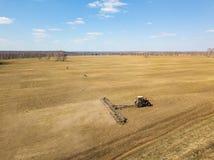 Antena del tractor rojo con una paleta arrastrada para segar y escardar los campos para la agroindustria del color amarillo debaj fotos de archivo libres de regalías