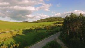 Antena del valle de la montaña con los caminos entre los campos verdes almacen de metraje de vídeo