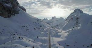 Antena delantera a lo largo del camino en valle nevoso en el paso de Valparola Puesta del sol o salida del sol soleada, cielo nub almacen de metraje de vídeo