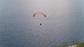 Antena depois dos Paragliders sobre o mar com ideia das montanhas e do verde 2 video estoque