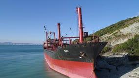 Antena dla holownik łodzi cumował na oceanu brzeg blisko wzgórza z zielonymi drzewami na niebieskiego nieba tle strzał czerwone zbiory