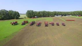 Antena do grupo de equipamentos agrícolas vermelhos que montam junto no campo arado vídeos de arquivo