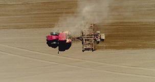 Antena do trator no campo da colheita que ploughing o campo agrícola filme