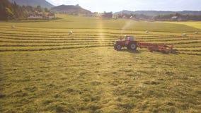 A antena do trator recolhe o feno no campo em um dia ensolarado da linha verde nas montanhas 4K filme
