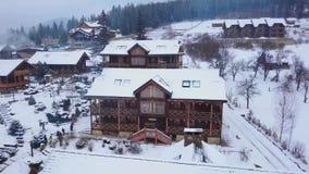 Antena drewniane chałupy w górskiej wiosce otaczającej z iglastym lasowym trutnia widokiem szalety zakrywający z śniegiem zdjęcie wideo