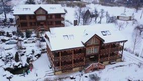 Antena drewniane chałupy w górskiej wiosce otaczającej z iglastym lasowym trutnia widokiem szalety zakrywający z śniegiem zbiory