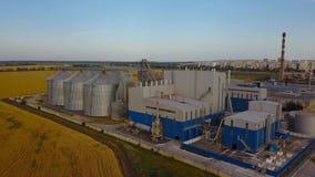 Antena duże stalowe zbożowych silosów windy składowe przy żółtym pszenicznym polem Rolnictwo przemysłu 4k powietrzny wideo zbiory wideo