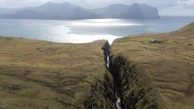 ANTENA: El volar a lo largo de una garganta rocosa estrecha que lleva hacia los mares abiertos extensos en Faroe Island espectacu almacen de metraje de vídeo