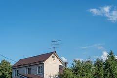 Antena en el tejado de una casa rural contra el cielo azul y las nubes blancas imagen de archivo libre de regalías