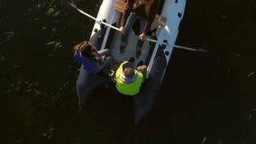 Antena: firma młodzi modnisie wiosłuje w nadmuchiwanej łodzi na spokojnym jeziorze HD slowmotion zdjęcie wideo