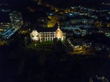 Antena, igreja iluminada na noite com casas da cidade Imagem de Stock Royalty Free