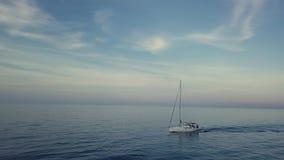 Antena imponente de la órbita 4k del barco de navegación a través del mar azul en cloudscape de la puesta del sol metrajes