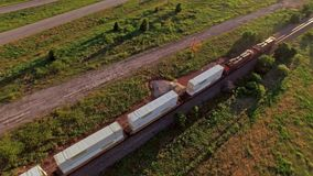 Antena impresionante de un tren de carga que pasa a través de campo metrajes