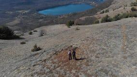 Antena: junte caminar en las montañas, los backpackers que caminan al aire libre visión panorámica, el viaje inspirador y la libe almacen de metraje de vídeo