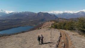 Antena: junte caminar en las montañas, los backpackers que caminan al aire libre visión panorámica, el viaje inspirador y la libe almacen de video