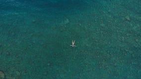 ANTENA: kobieta unosi się na błękitne wody powierzchni, pływa w przejrzystym morzu śródziemnomorskim, wierzchołka puszka widok, w zdjęcia royalty free