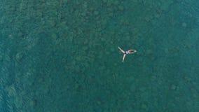 ANTENA: kobieta unosi się na błękitne wody powierzchni, pływa w przejrzystym morzu śródziemnomorskim, wierzchołka puszka widok, w fotografia stock
