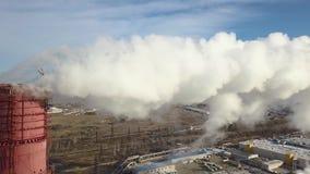 ANTENA: La zona industrial con un humo blanco grueso grande del tubo rojo y blanco se vierte del tubo de la fábrica en contraste  almacen de video