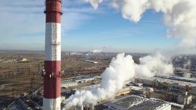 ANTENA: La zona industrial con un humo blanco grueso grande del tubo rojo y blanco se vierte del tubo de la fábrica en contraste  metrajes