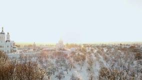 Antena: latać nad samochodowy jeżdżenie przez śnieżnego lasu przy złotym zimy wschód słońca Ludzie na zimy wycieczki samochodowej zbiory