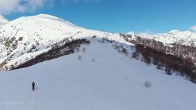 Antena: latający nad wycieczkowicza odprowadzeniem w kierunku śnieżnego góra wierzchołka, narciarskiego krajoznawczego mountainee zbiory wideo