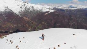 Antena: latający nad wycieczkowicza odprowadzeniem w kierunku śnieżnego góra wierzchołka, narciarskiego krajoznawczego mountainee zdjęcie wideo