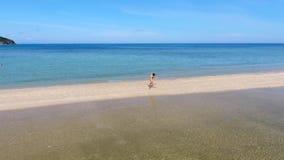 Antena: Menina bronzeada feliz no biquini que corre em Sandy Spit Beach Modelo bonito Jogging Outdoors da aptidão da raça mistura video estoque