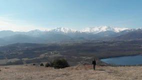 Antena: mujer que camina en las montañas, el backpacker que camina al aire libre visión panorámica, el viaje inspirador y la libe metrajes